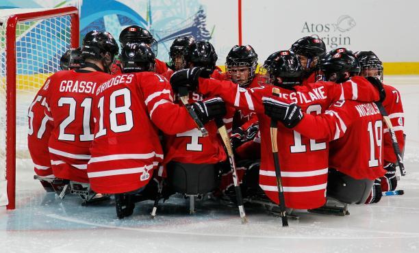 The Canadian Ice Sledge Hockey Team gathered around the goal.