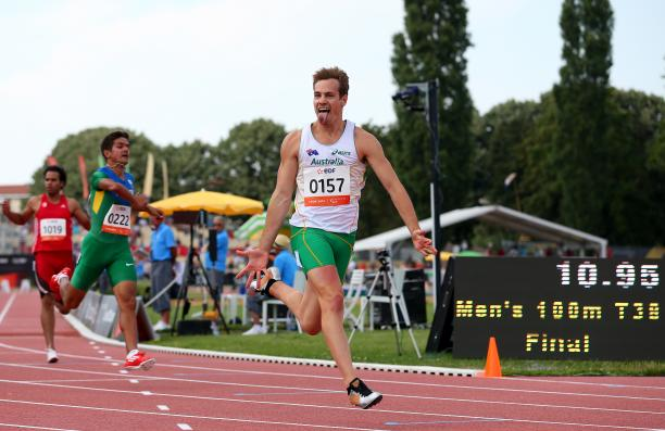 Man crossing a finish line in a stadium, celebrating