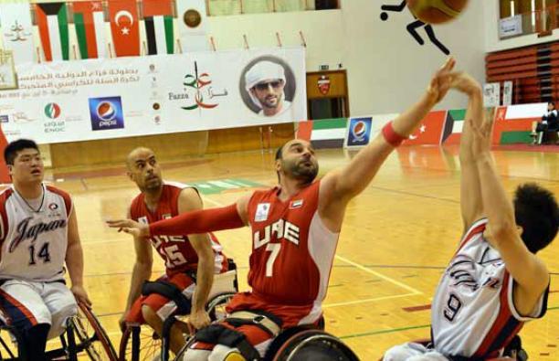 A man in a wheelchair shoots a basketball layup.