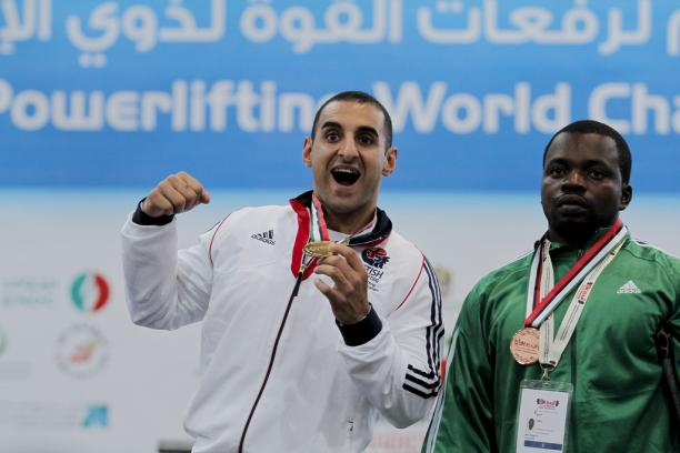 An athlete poses showing his gold medal.