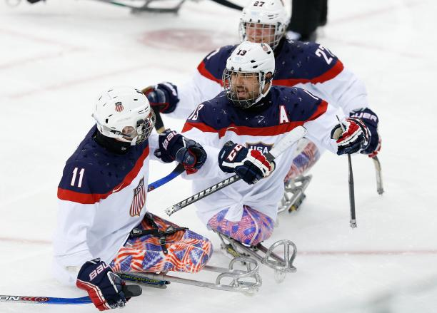 An ice sledge hockey player skates up to his teammate to celebrate.