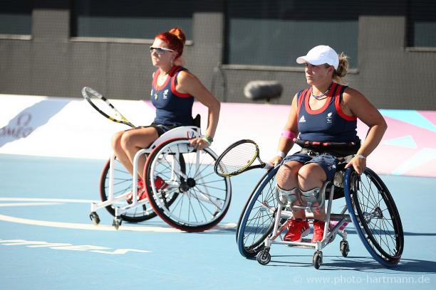 Two women in wheelchairs with tennis rackets during a match