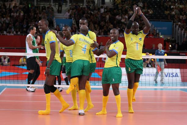 Six men celebrating on a volleyball field.