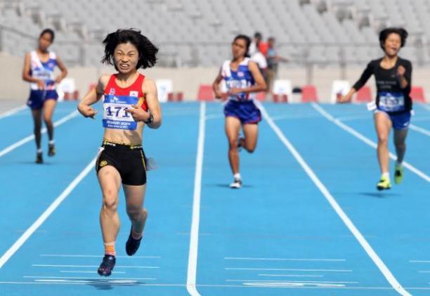 Female runner crosses the finish line on a blue track in a stadium, celebrating
