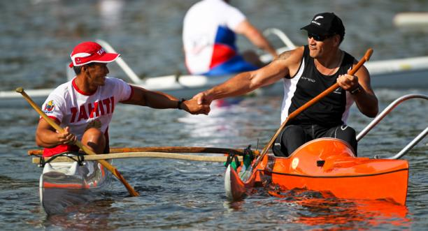 A picture of 2 men in a canoe shaking their hands celebrating a victory