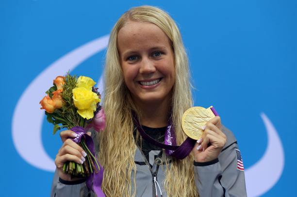 A picture foa a blonde woman showing her gold medal hanging around her neck