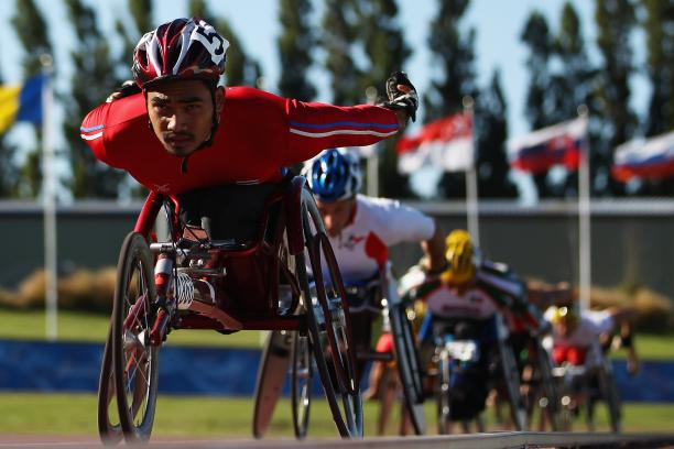 A picture of a man in a wheelchair racing on a track