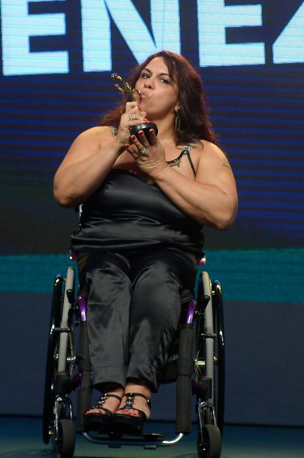 Women in black dress sitting in a wheelchair kissing a trophy