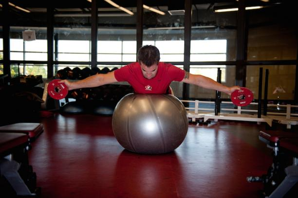 An athlete lies on his stomach on a stability ball with both his arms stretched out to the sides holding weights.