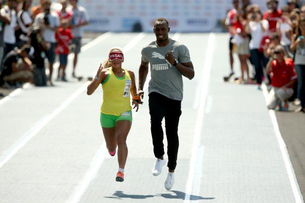 Brazilian Paralympian Terezinha Guilhermina runs with Usain Bolt of Jamaica as her guide during an exhibition in preparation for the Mano a Mano Athletics Challenge at the Jockey Club Brasileiro in Rio de Janeiro, Brazil.
