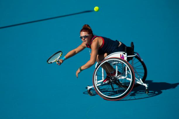 Woman in a wheelchair on a blue tennis court trying to reach a ball
