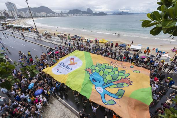 Crowd of people from above, holding a huge banner with Rio motives