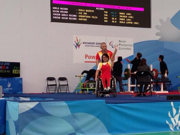 Women in wheelchair waving in front of a bench press