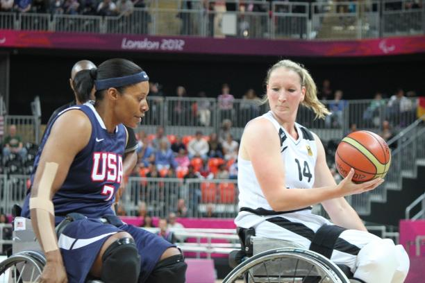 Two women in wheelchairs, playing basketball, fighting for the ball