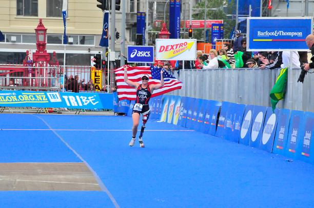 A picture of a woman with a prosthesis wearing an American flag to celebrate her victory