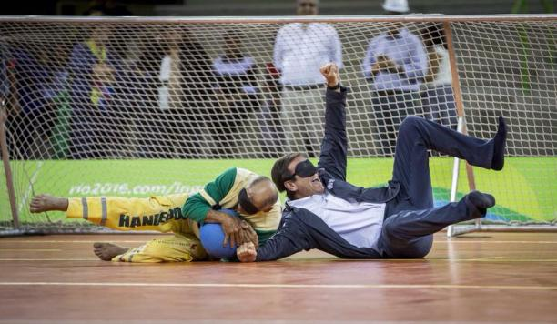Two blindfolded men, one in a suit lying on a field of play, catching a ball