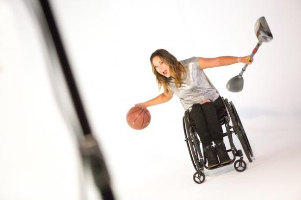 Woman in wheelchair with a basketball and a paddle in her hands