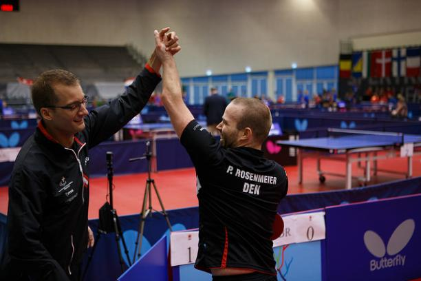 Two table tennis players celebrate.