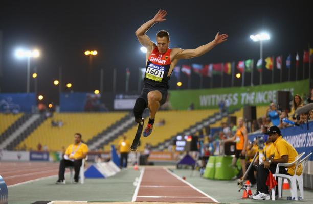 a male from Germany wearing red and black clothes competing in the long jump