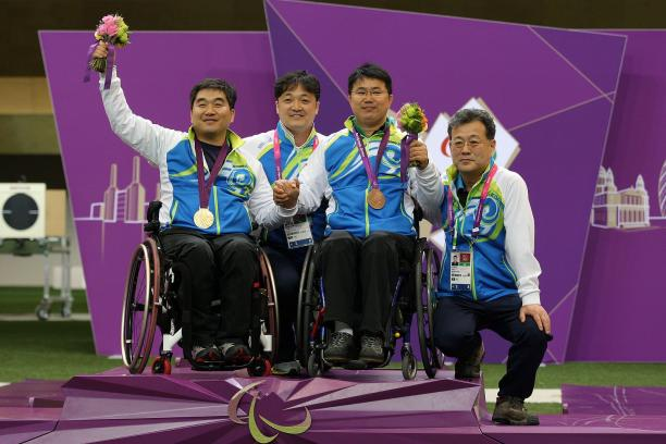 Four athletes in a wheelchair on a podium celebrating their medals.