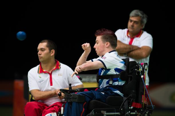 Two men in wheelchairs, one throwing a blue ball