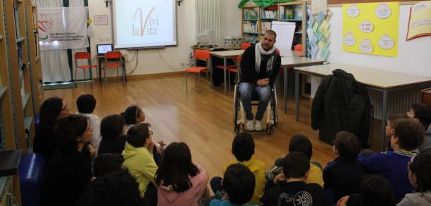 Man in a wheelchair talking to a class of school children