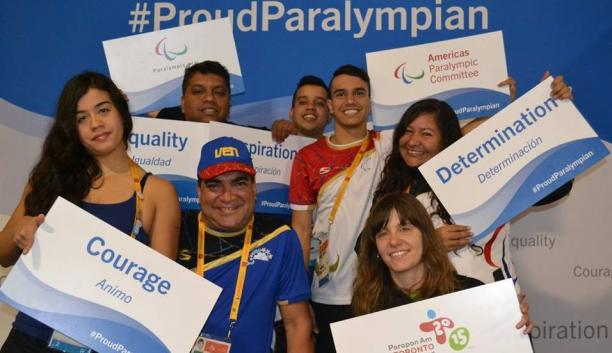 Group picture of four people, smiling and holding signs with 'ProudParalympian'