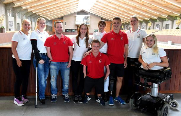 Fifteen Danish Para athletes pose for a photo wearing the red and white Danish colours.