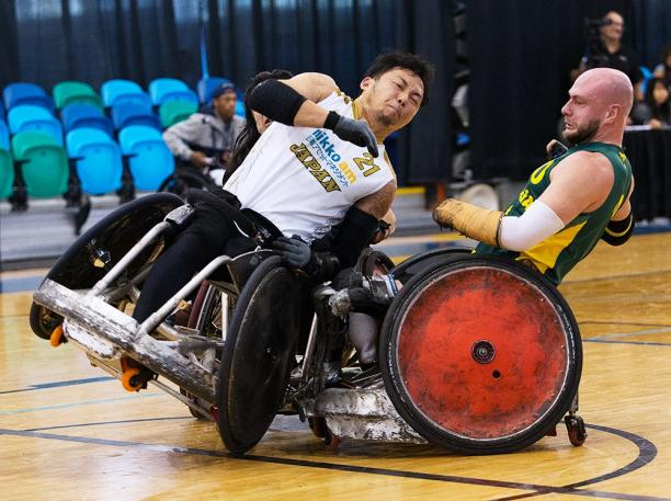 Two men playing wheelchair rugby collide their chairs.