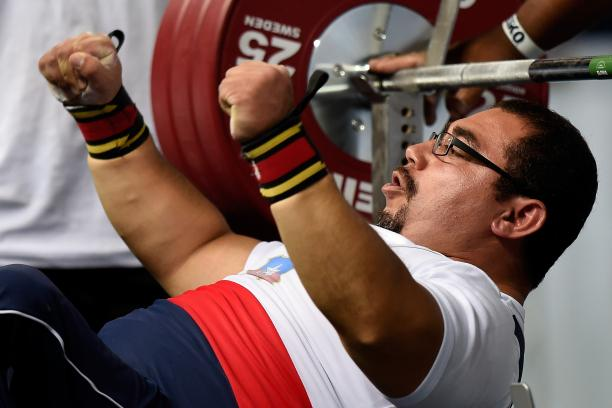 Chilean powerlifter Juan Carlos Garrido is on the bench and raises his hands celebrating his win.
