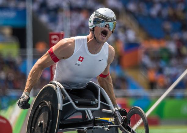 A wheelchair racer celebrates winning gold