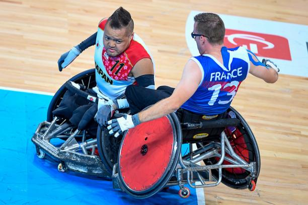 Two wheelchair rugby players crashing into each other