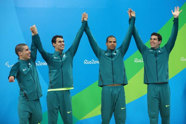 Four Brazilian swimmers on a podium celebrating