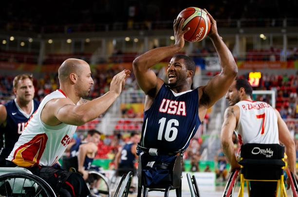 Man in wheelchair holds a basketball in the air away from his defender