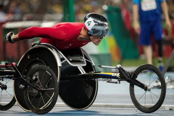 Close up of a wheelchair racer with a red racing suit and a silver helmet.