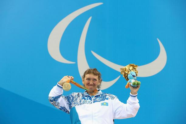 Woman on podium in a wheelchair, showing a medal