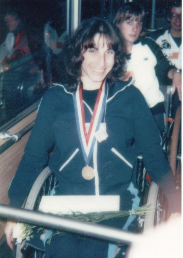 Photo of a woman in a wheelchair with a medal around her neck. The photo looks very old