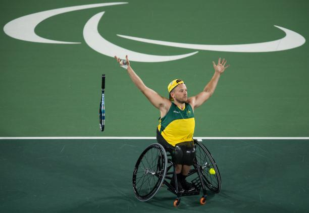 man in wheelchair throws away his tennis racket and raises his arms to celebrate