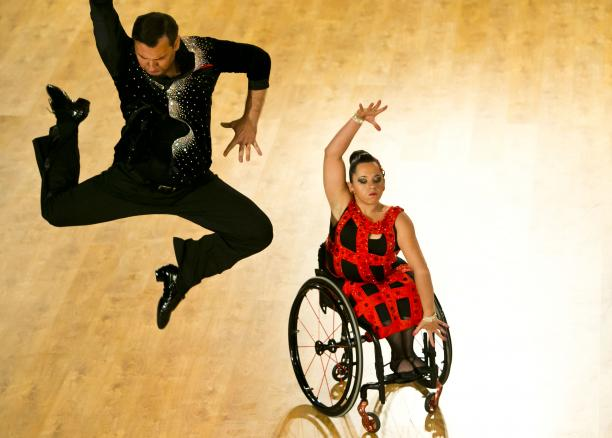 A woman in wheelchair dances with her stand-up partner who is jumping