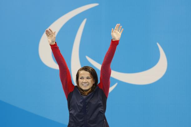 Upper body of a woman, raising her arms in the air