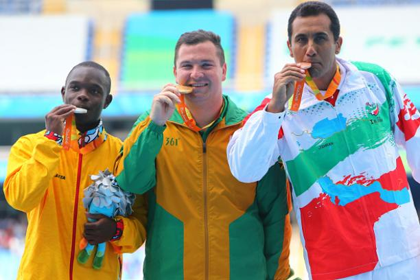 Three men on podium, with their medals