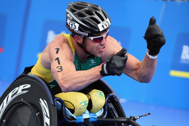 A picture of a man in a wheelchair celebrating his victory after a para-triathlon