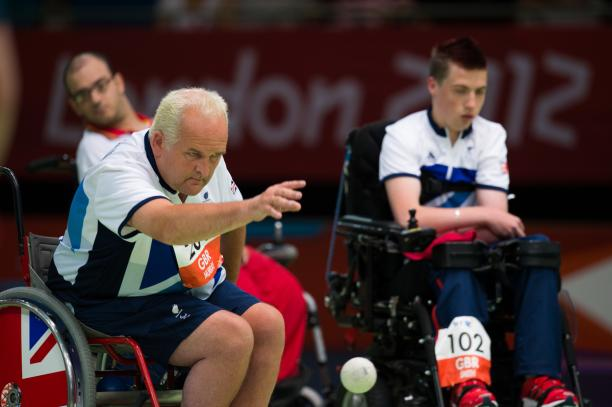 Two men in wheelchairs on a boccia field of play