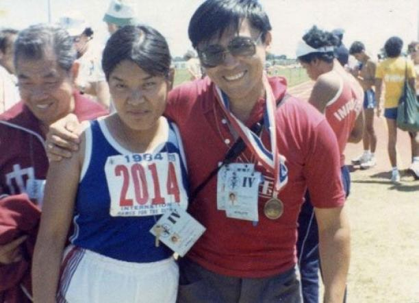 Two people posing for a photo in track clothes