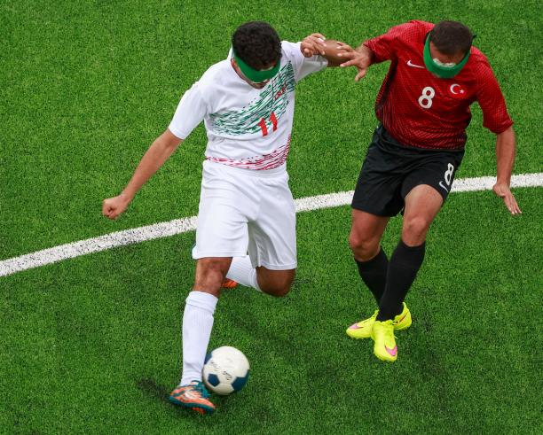 Two blind footballers fighting for the ball