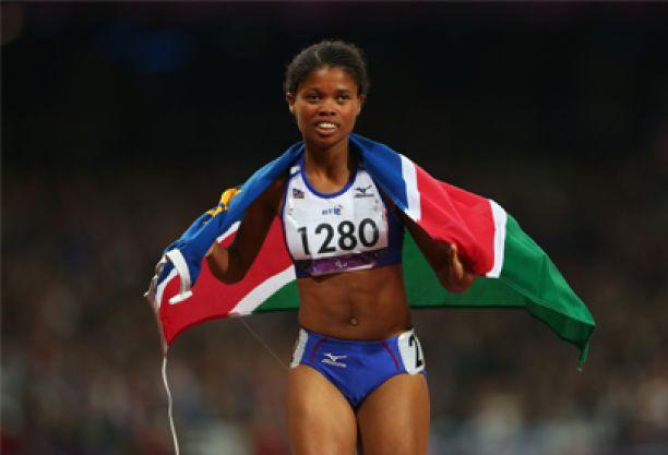 A picture of a woman running with a Namibian flag on her shoulder