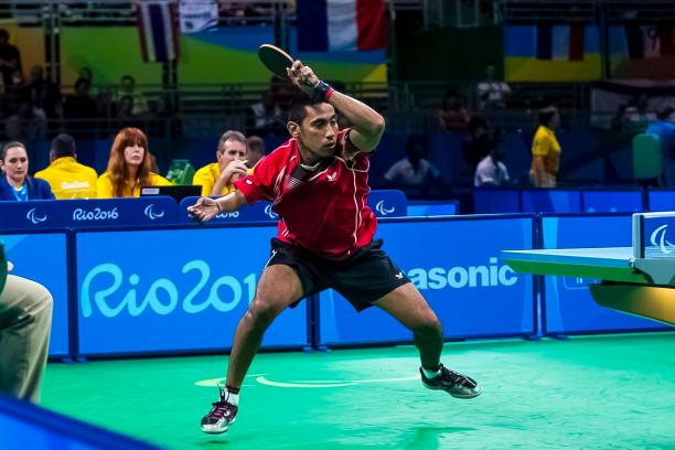 a para table tennis player hits the ball across the net