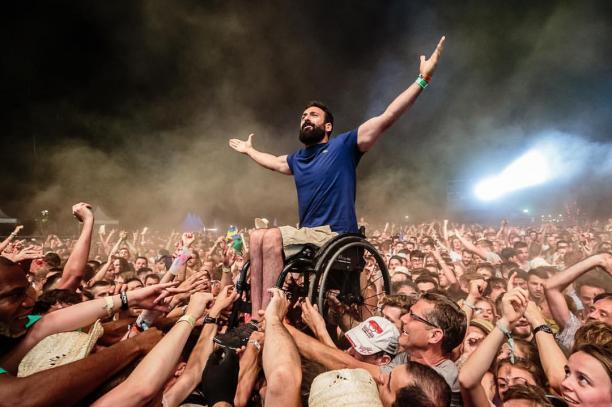 a man in a wheelchair crowd surfs