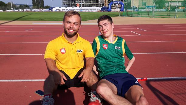 two male para athletes sit together on the track