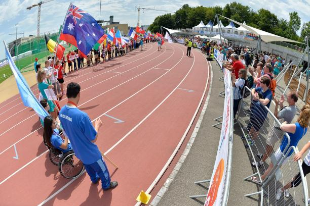 Teams holding flags on the track for Opening Ceremony
